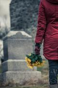 Close-up of a Sad in front of a Gravestone. Stock Photos