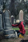 Sad Woman in Mourning Touching a loved one's Gravestone - stock photo