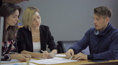 French friends are discussing a plan to build houses together in a modern office Stock Footage