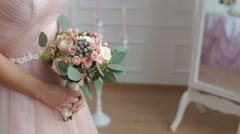 Bride in dusty pink dress. Hands with a bouquet Stock Footage