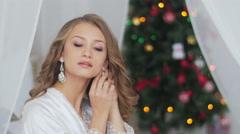 Beautiful young girl in underwear and bathrobe in earrings Stock Footage