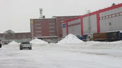 Passenger car rides in the winter when the snow on the road warehouse area Stock Footage