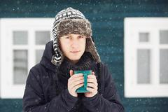 Portrait of young man outdoors in winter under snowstorm - stock photo