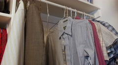 Dolly shot of a man hanging up shirts in his closet - stock footage