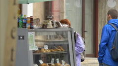 Two people standing next to a food stall on a street in Brasov Stock Footage