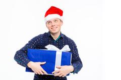 Excited anticipated male in santa claus hat holding gift Stock Photos