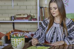 Young Romanian woman in traditional costume painting - stock photo