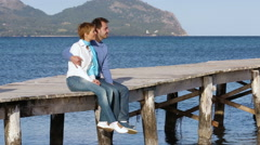 Beautiful couple sitting on the jetty enjoying time together Stock Footage