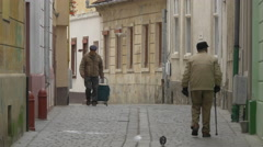 Elderly men walking on a narrow street in Brasov Stock Footage