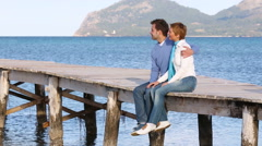 Beautiful couple sitting on the jetty enjoying the day Stock Footage