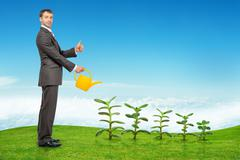 Businessman watering plants and showing ok - stock photo