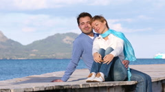 Young couple sitting on the jetty Stock Footage