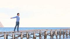 Young man staying on the jetty opening his arms Stock Footage