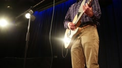 Young guitarist playing an electric guitar on stage with lighting - stock footage