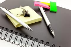 personal organizer, post-its, pen, pencil and steel clip - stock photo