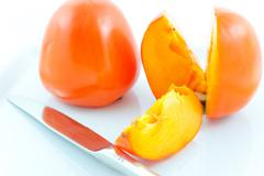 Two ripe persimmons and steel knife Stock Photos