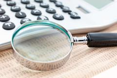 financial newspaper with calculator and magnifier - stock photo