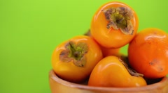 Beautiful ripe persimmon in wooden plate Stock Footage