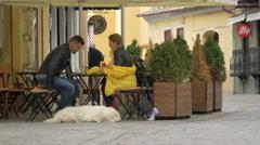 Couple sitting at an outdoor restaurant on Saint John street, Brasov Stock Footage