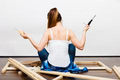 Woman assembling wooden furniture. DIY. Rear view. - stock photo