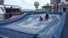 Cruise ship recreation teenager learn to surf pool 4K Stock Footage