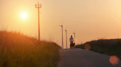 Man and dog at a field with sundown and wind turbine Stock Footage