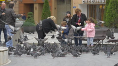 Childern feeding pigeons in Council Square, Brasov - stock footage