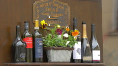 Bottles of wine and a flower pot on a street in Brasov Stock Footage