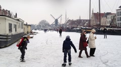 Iceskating in Holland old house windmill Stock Footage