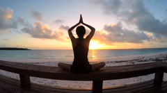 Young girl practicing yoga outdoors at sunrise Stock Footage