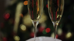bubbles of champagne in glasses on the background of the Christmas tree - stock footage
