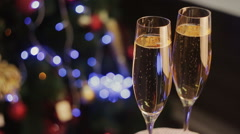 Pair of champagne glasses, Christmas tree ornament as the background Stock Footage