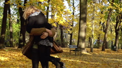 Couple cuddling and having fun in the park, slow motion shot - stock footage