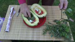 Gardener placing herbs  in pumpkin and preparing to cook it with foil Stock Footage