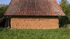 Old rustic barn with clay wall in meadow in village Stock Footage