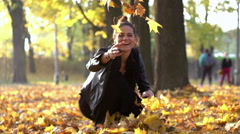 Woman throwing leaves in the air and smiling to the camera, slow motion shot Stock Footage