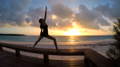 Girl in silhouette practicing yoga outdoor - stock footage