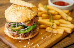 Home made burgers on wooden background Stock Photos