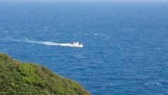 Small boat on cyan waters of East China Sea, hillside grass on foreground Stock Footage
