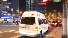 Ambulance car pass intersection, busy traffic junction night time Stock Footage