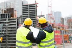 Back turned workers talking at construction site reviewing plans Stock Photos