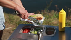 Cooking hot dogs with fresh vegetables at a street kitchen Stock Footage
