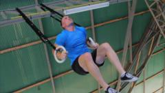 Athlete Performing Muscle Ups On Gymnastics Rings Training Workout Low Angle Stock Footage