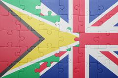 puzzle with the national flag of great britain and guyana - stock photo
