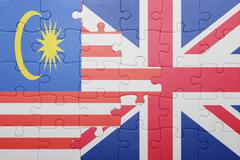 puzzle with the national flag of great britain and  malaysia - stock photo