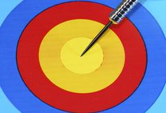 Dart needle in the center of the target - stock photo