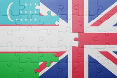 Puzzle with the national flag of great britain and uzbekistan Stock Photos