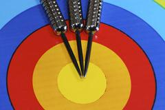 Three Dart needles in the center of the target - stock photo
