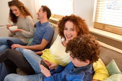 Happy family sitting on sofa enjoying tim together Stock Photos