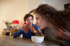 Brother and sister sitting at dining room table eating food - stock photo
